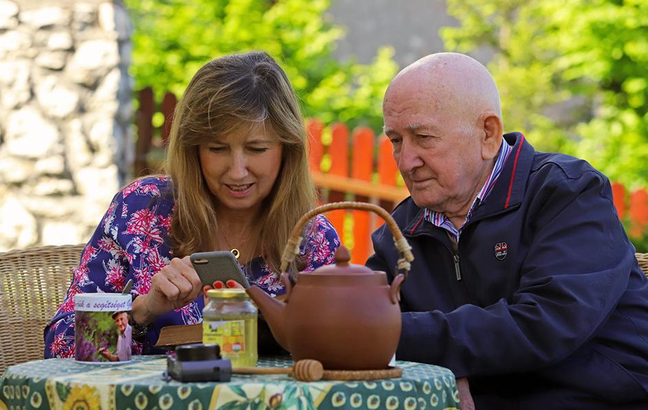 Gyuri bácsi és Zsuzsa a kertben nézik a mobilaplikációt